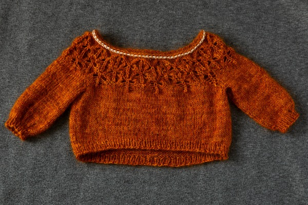 An orange lace yoke sweater with the neckline on white waste yarn.
