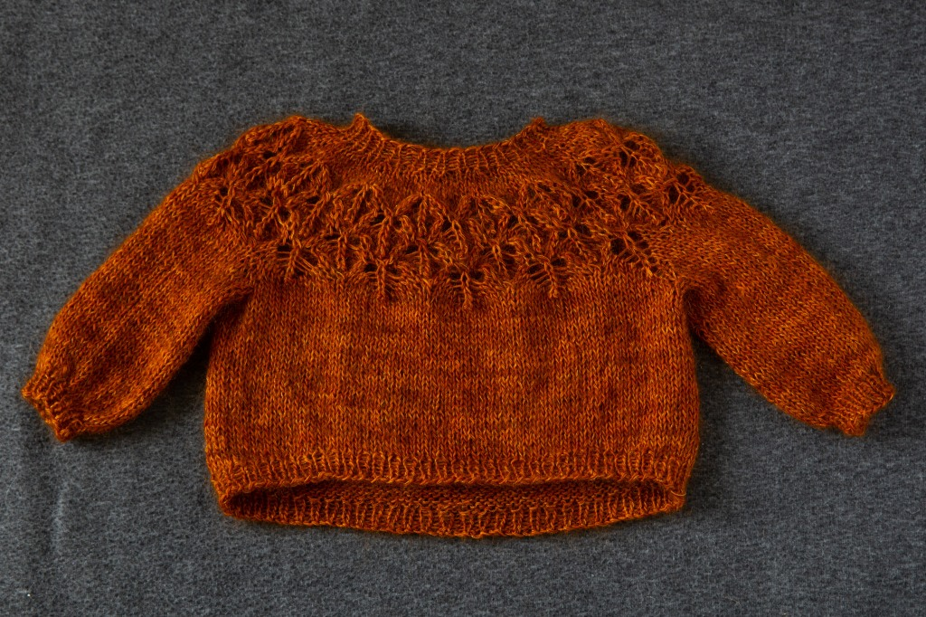 An orange finished lace yoke sweater. Before it has been blocked.