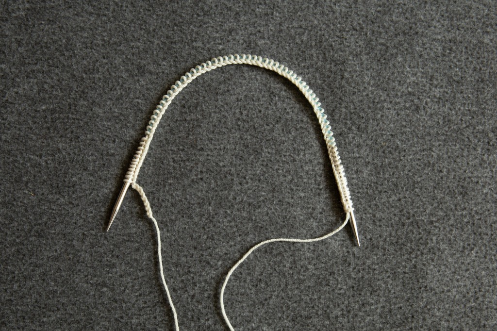a circular needle with provisional cast on in white yarn