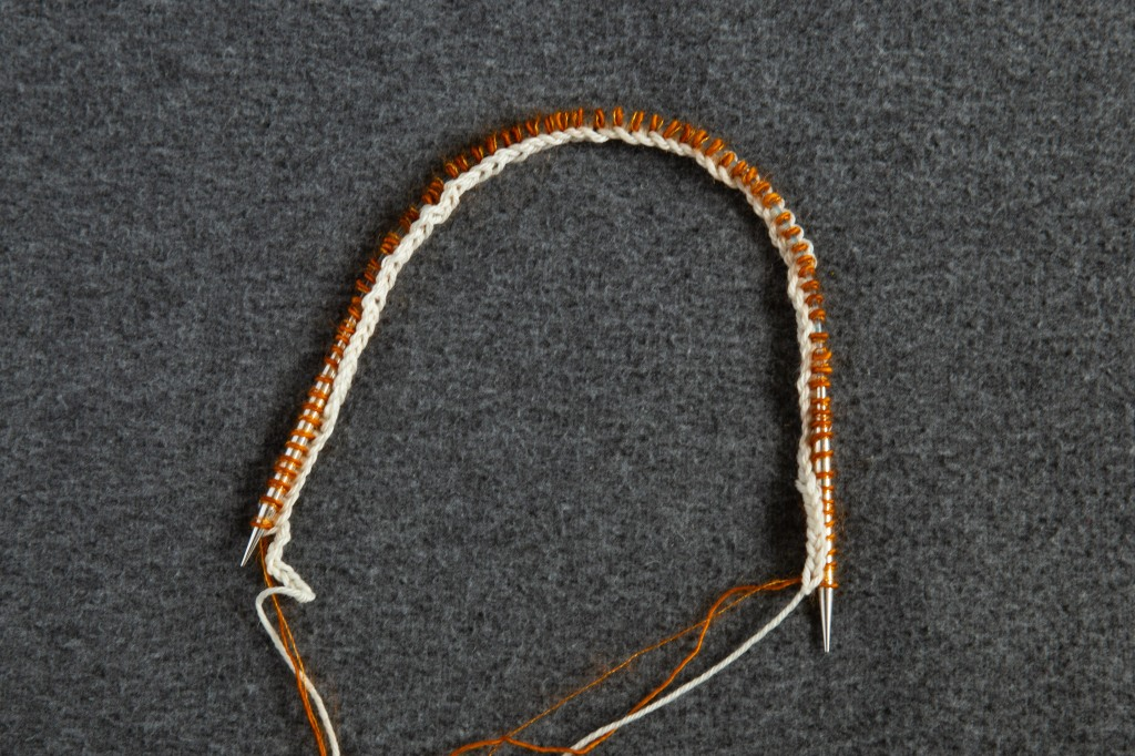 a circular needle with provisional cast on in white yarn and first row knit in copper colour yarn