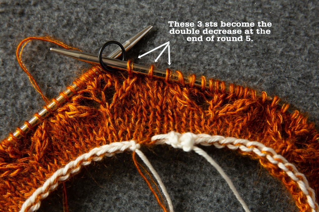 knitting project in progress, with a stitch marker, and annotation showing the final three stitches of the round to decrease