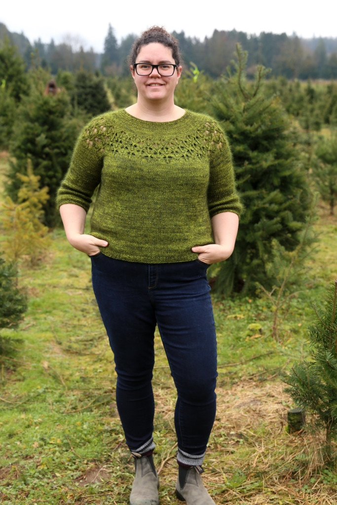 Alexa is standing in a field of trees wearing her green lace yoke jumper with her hands in her pockets. Her sweater hits just above the pockets of her jeans.