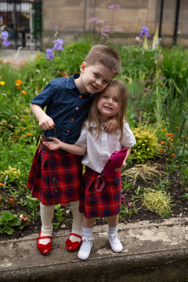 Two smiling kids in kilts and button-down shirts