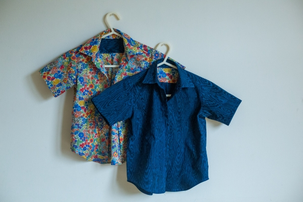 two child shirts hanging on a wall