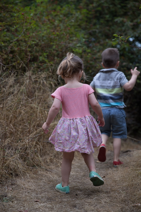 children running away along a forest path, one wearing a dress in striped and floral fabrics