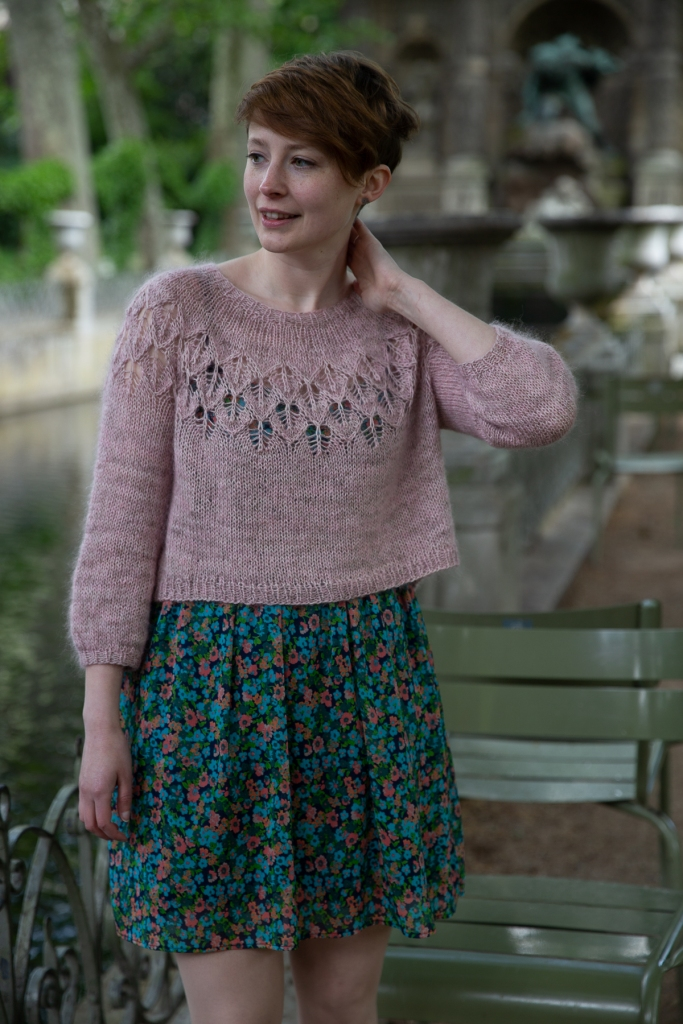 Nina is wearing a soft pink lace yoke sweater over a floral print dress that hits just above the knee. Her sweater is short, ending above her waist.