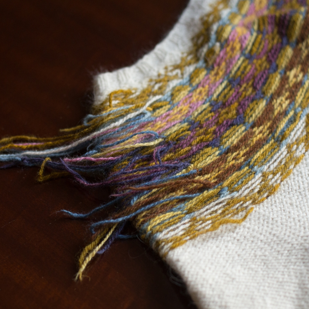 Detail of the inside of a colourwork sweater yoke with dozens of hanging yarn ends.