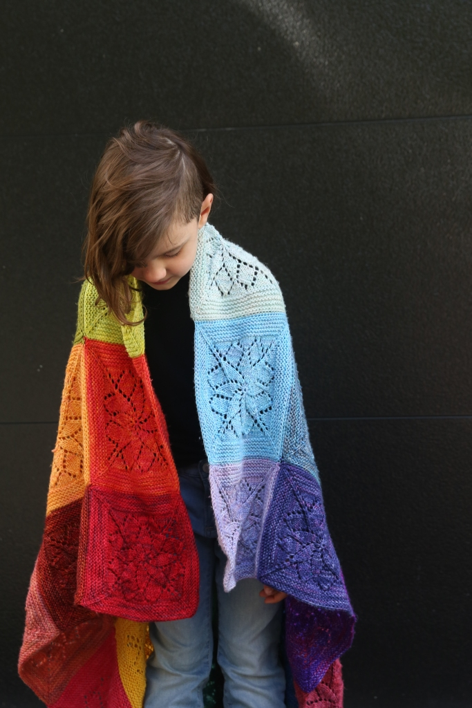 6-year-old Bodhi is standing with her blanket of rainbow squares wrapped around her. She is looking down at the ground.
