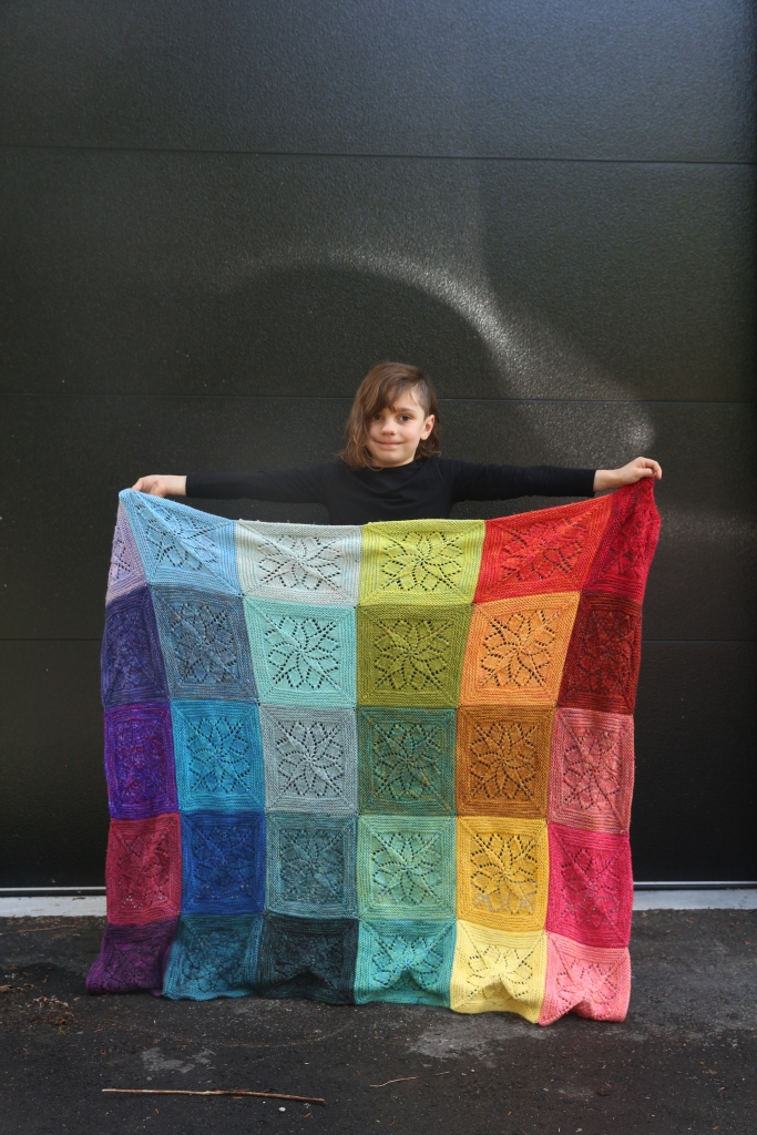 Bodhi is standing with her arms stretched out, showing off her full blanket of rainbow lace squares.
