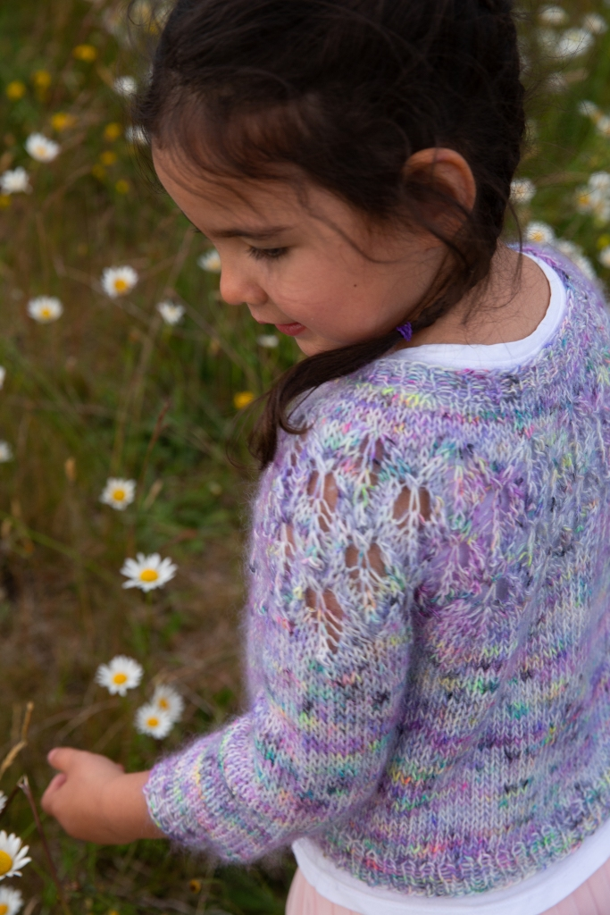 Olivia is wearing her lave yoke sweater, purple with a rainbow of speckles. She has braids in her hair and she is in a field of daisies.
