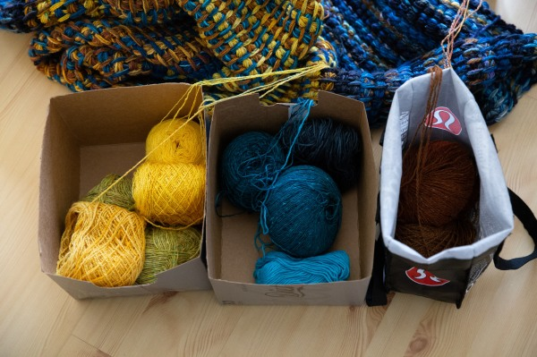 Boxes of yellow, blue, brown yarns and Tunisian crochet blanket in progress