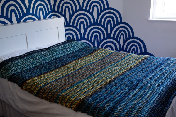 Tunisian crochet blanket in shades of blue and yellow on a bed