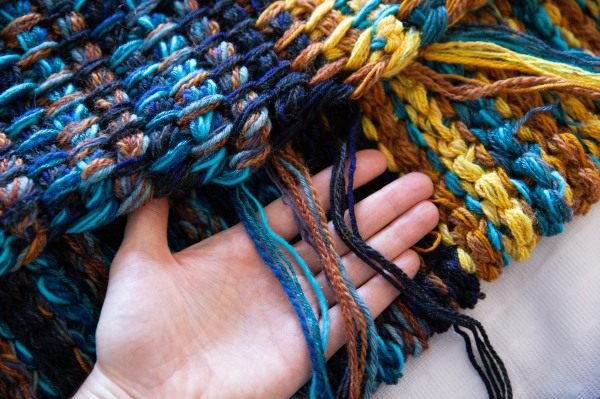 Edge of Tunisian crochet blanket in shades of blue and yellow, with woman's hand