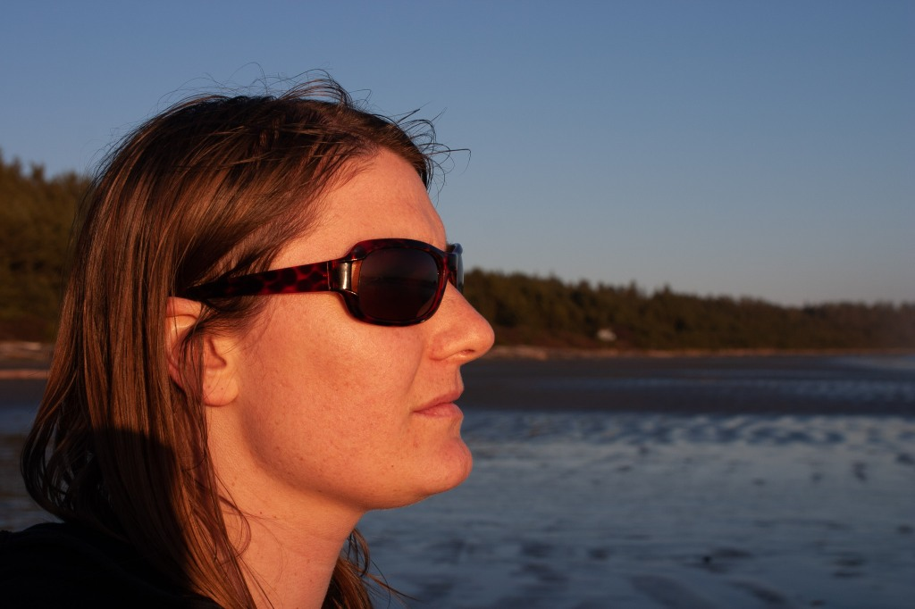 A close up of Emily wearing sunglasses and gazing into the distance. Beach and forest blurred in the background.
