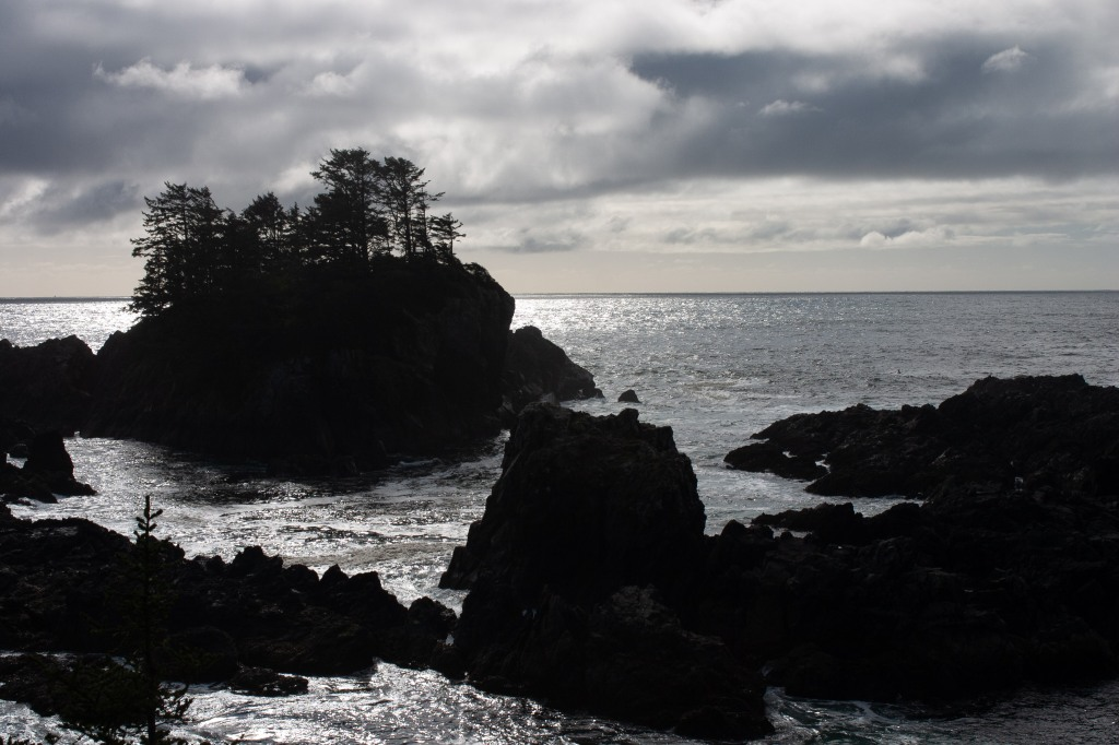 A moody photo of little rocky islands in the ocean. Clouds pass overhead.