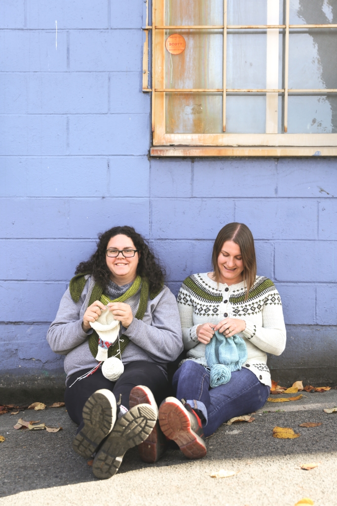 Emily and Alexa are sitting on the sidewalk with a vivid blue building behind them. They are each knitting. Emily is looking down at her knitting and Alexa is smiling at the camera.
