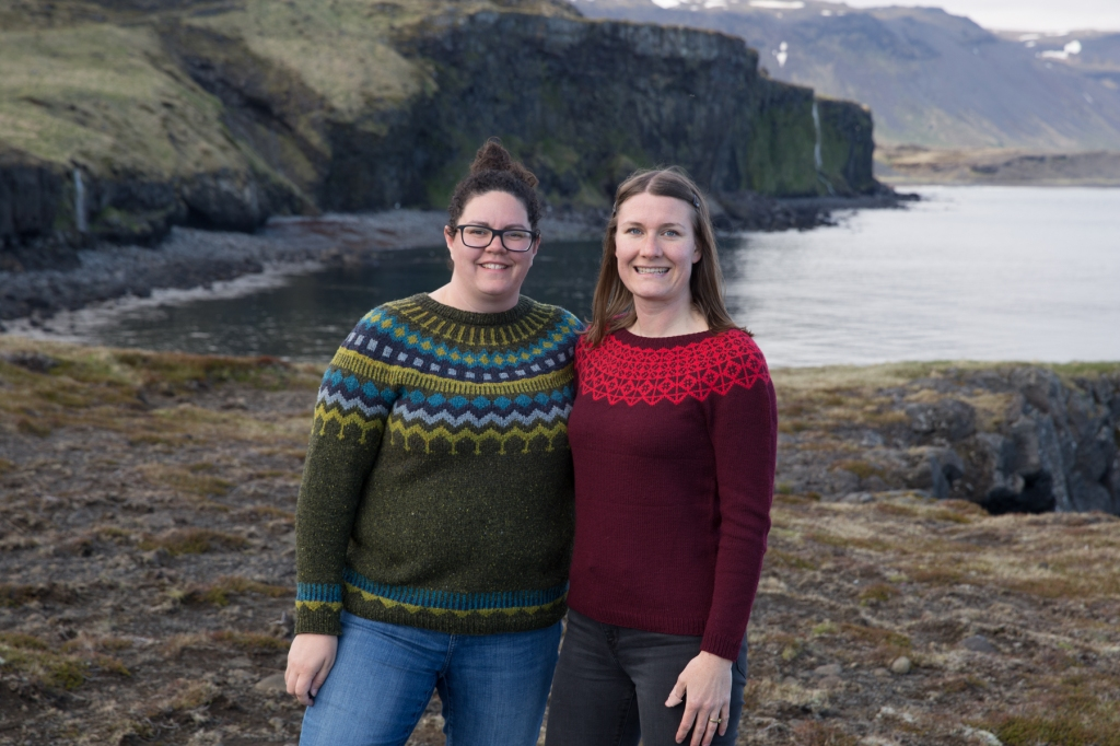 Emily and Alexa are standing near a cliff in hand knit sweaters. They are smiling with arms around each other. Emily's sweater is a deep maroon with a bright red colourwork yoke, Alexa's sweater is a warm dark green with pops of navy, bright teal, and chartreuse at the yoke.