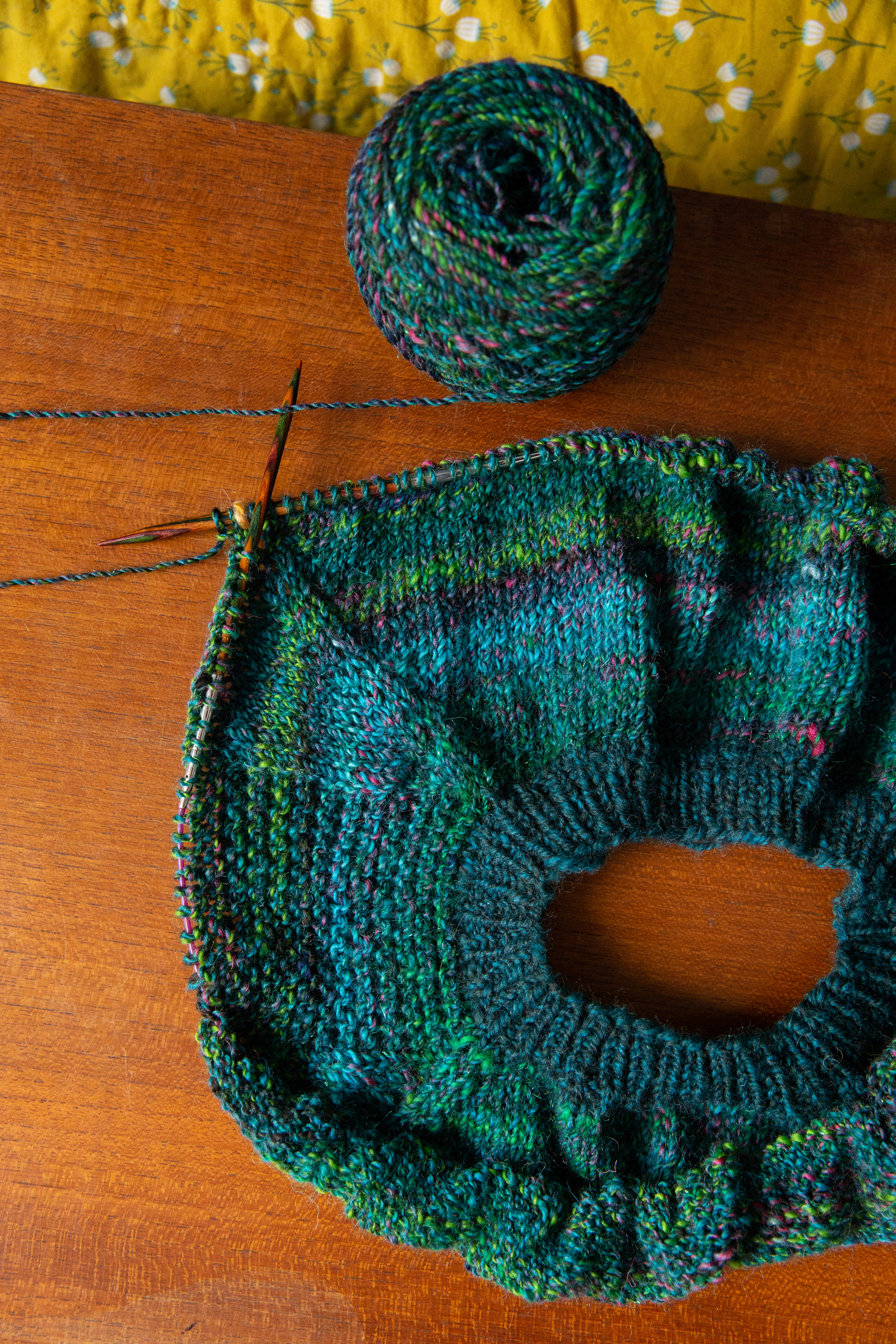 green and teal handspun raglan sweater yoke on the needles with a yarn ball