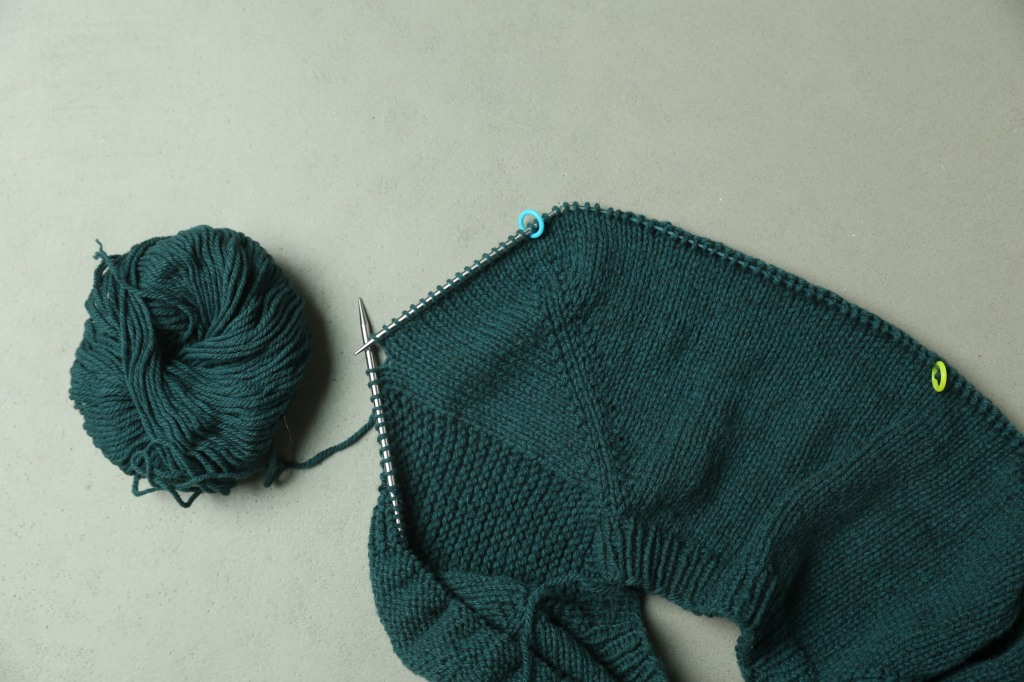 Close up showing the sweater yoke with 2 markers.