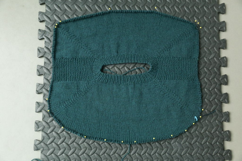 View from above of a sweater yoke pinned to a blocking board. There is a distinct wedge of fabric at the back of the sweater where the short rows were worked.