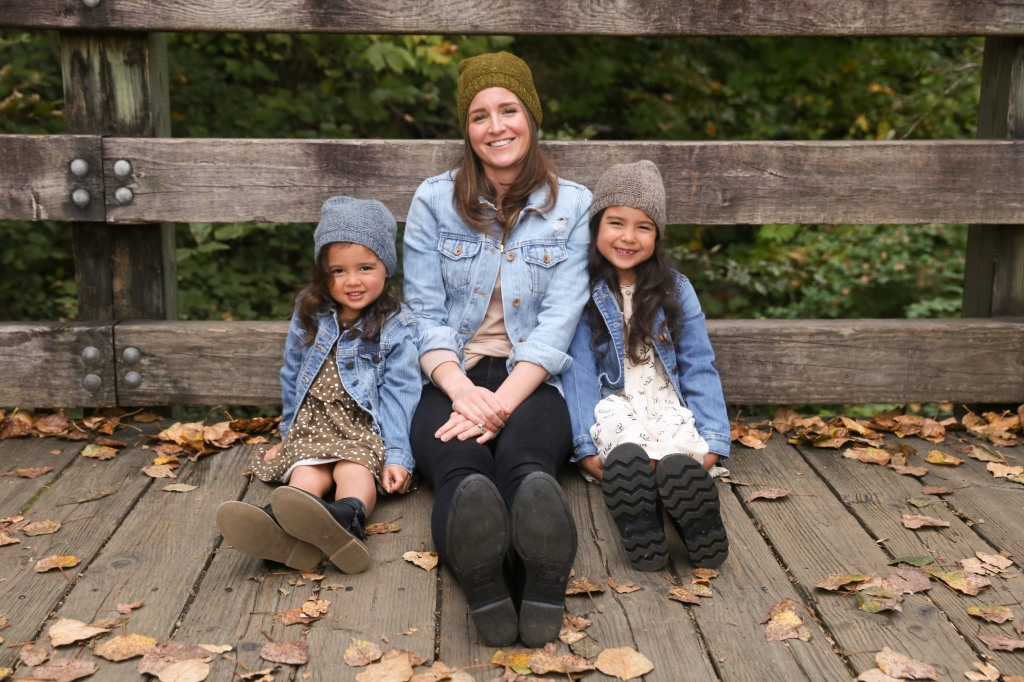 a woman and 2 children sitting on a bridge wearing knit hats