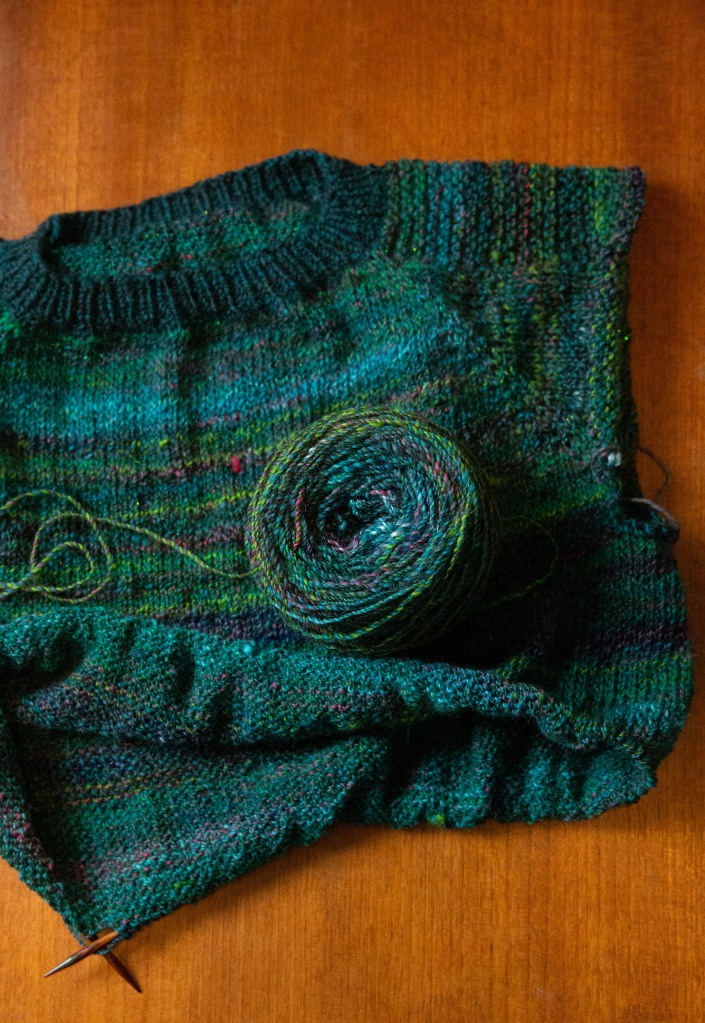 green and teal handspun raglan sweater in progress with yarn cake