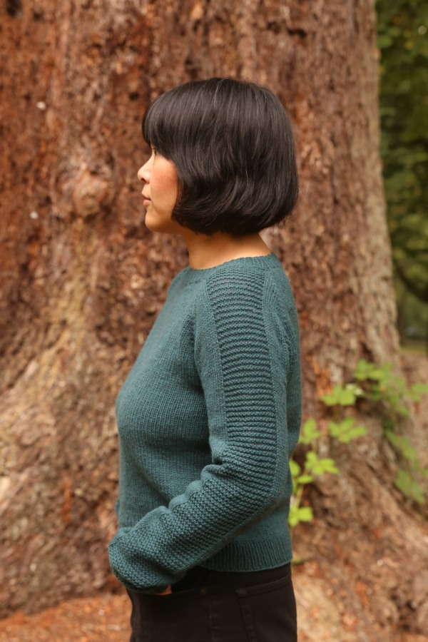 A woman in a hand knit sweater.
