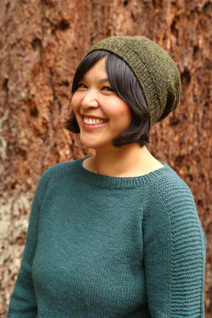 A woman in a hand knit sweater and hat.