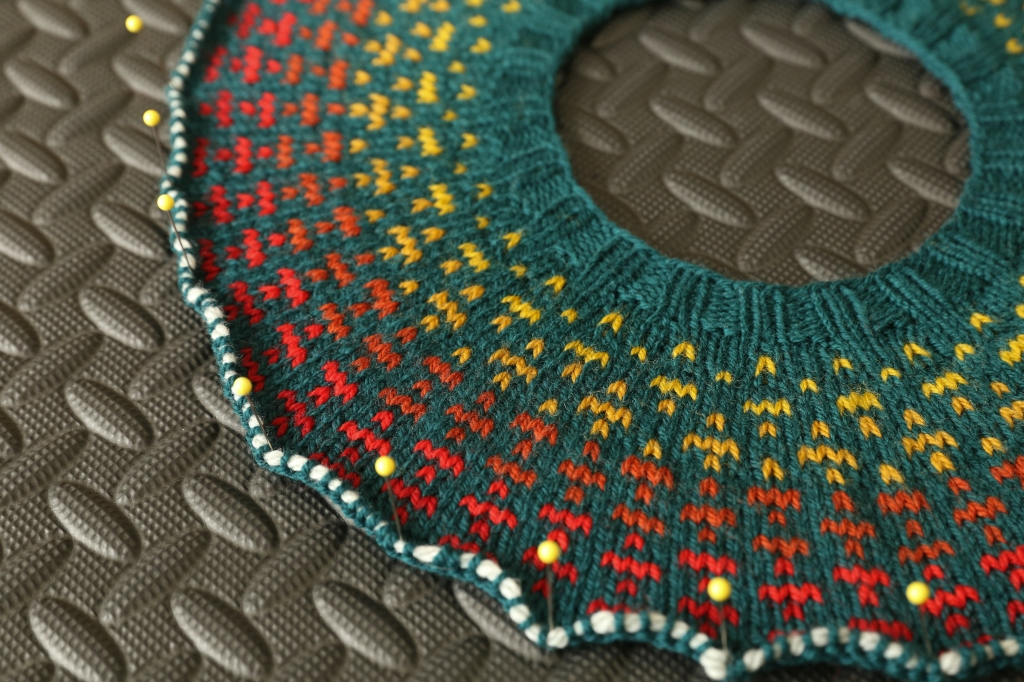 the yoke of a colourwork sweater pinned to a blocking board