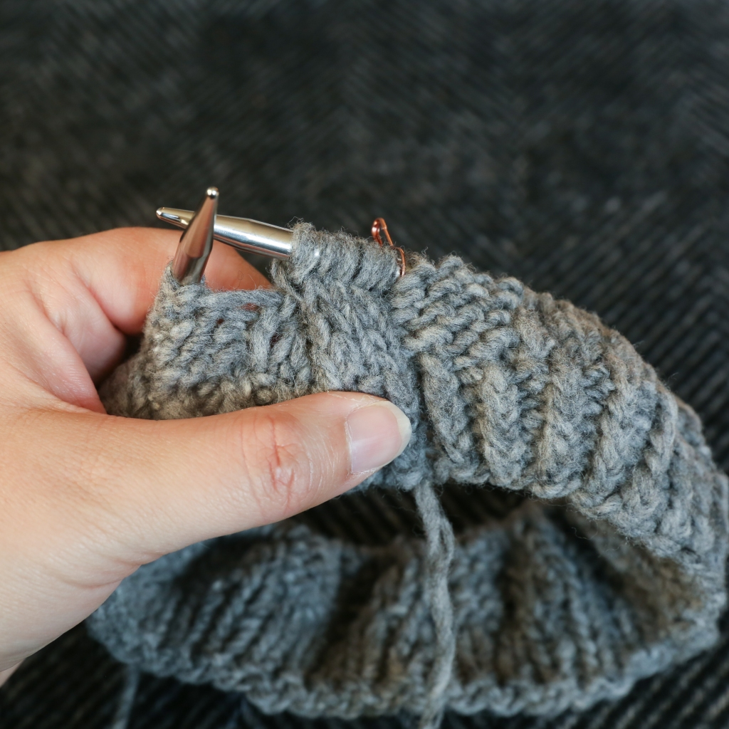 hands holding a grey hat in progress with a cable in it