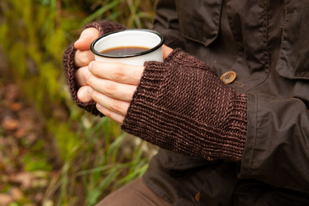 A man's hands in knit fingerless mittens holding a cup of coffee.