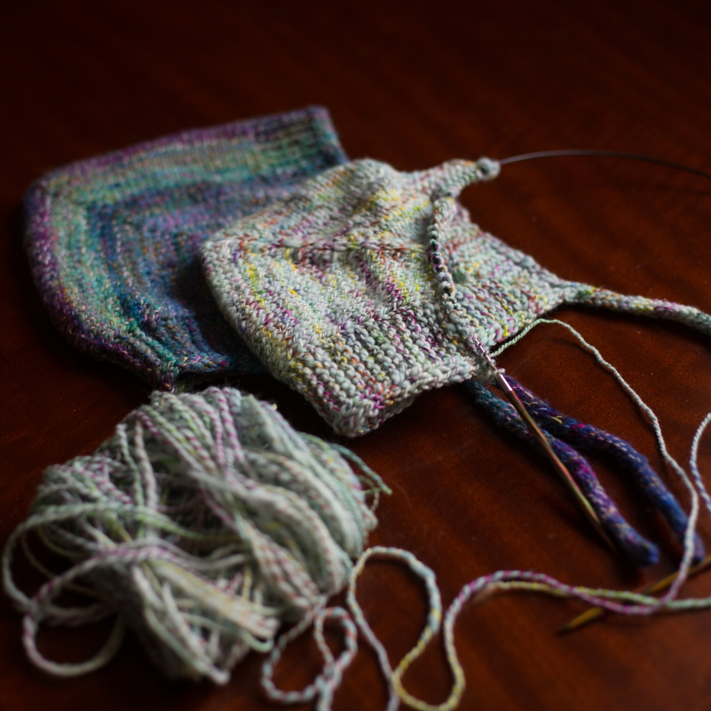 one bonnet and one bonnet in progress with yarn ball attached