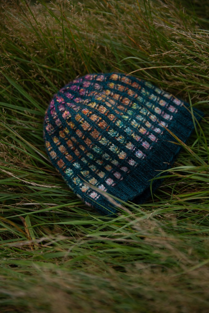 A colourwork hat on the grass