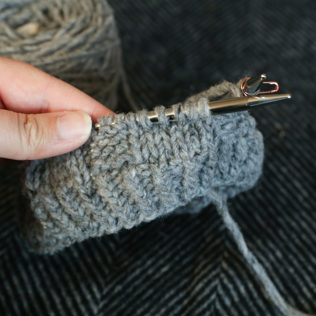 a knit hat in progress on the needles