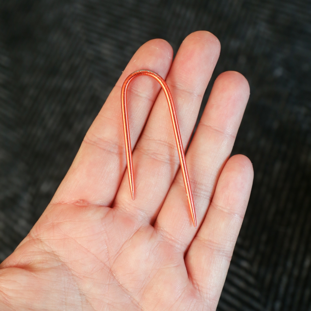 a hand holding a cable needle