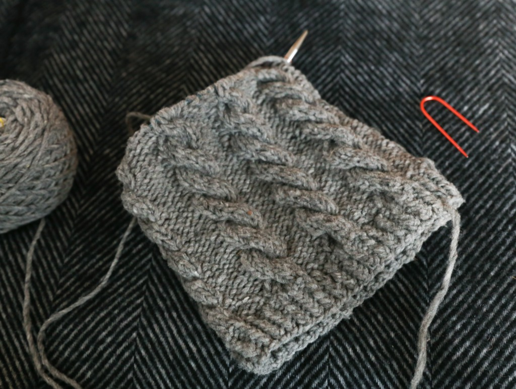 a cabled hat on the needles