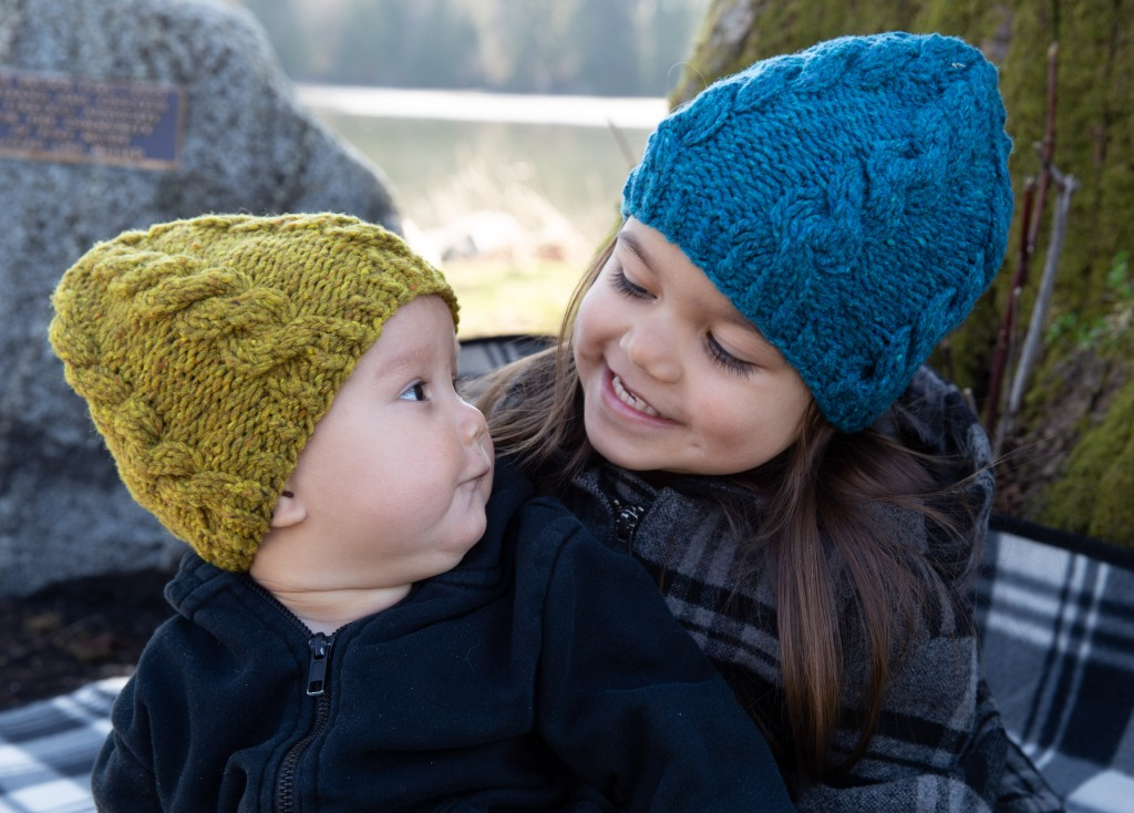 two children in cabled knit hats
