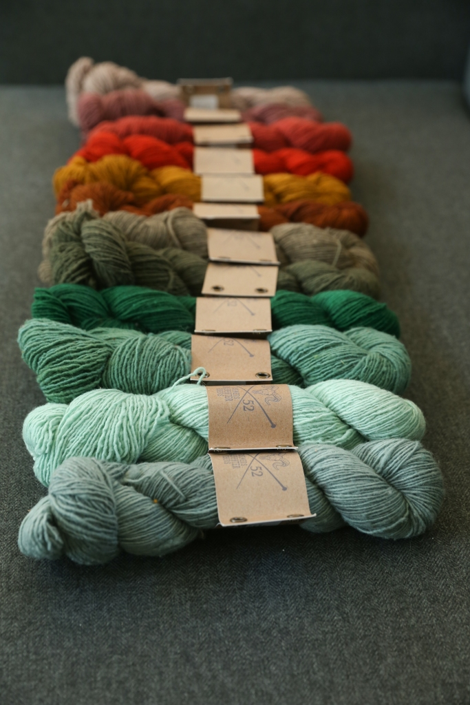 A warm rainbow of yarn skeins lined up.