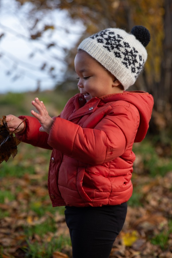 toddler playing with leaves wearing colourwork hat