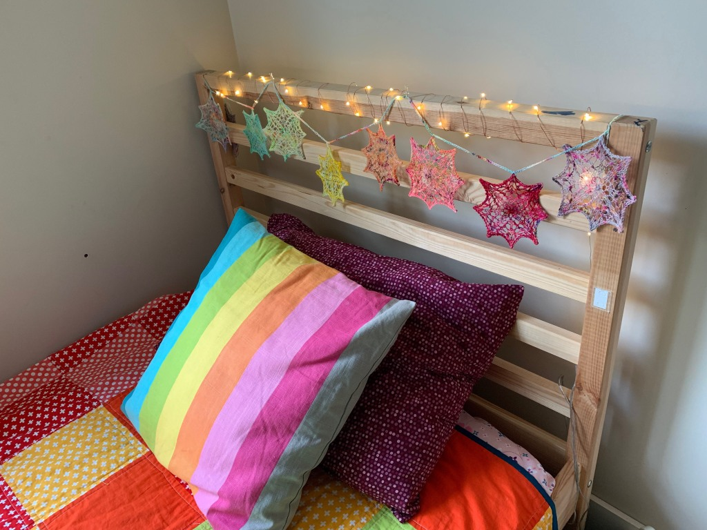 a bed with colourful lace snowflakes on the headboard