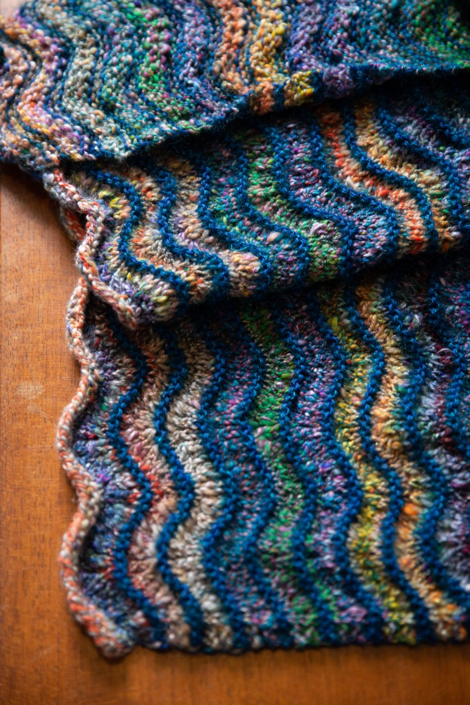 A wave-pattern blanket knit in handspun with contrast-colour stripes.