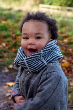 smiling toddler in a striped cowl
