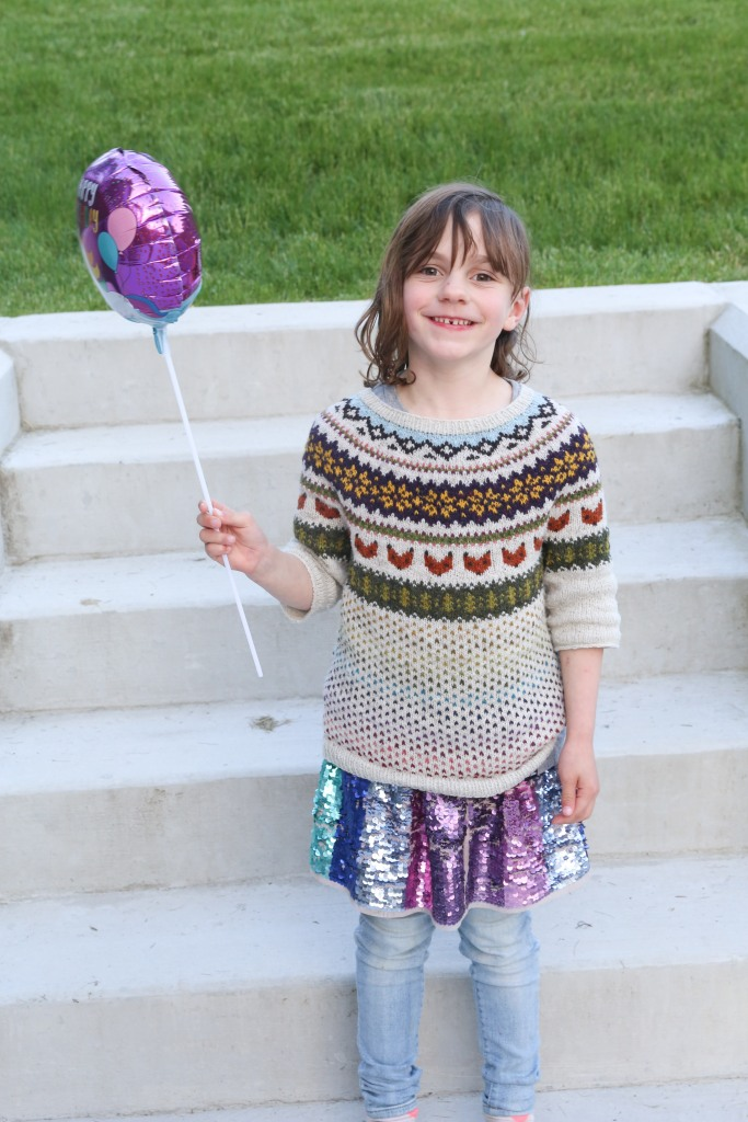 a smiling child in a colourwork sweater