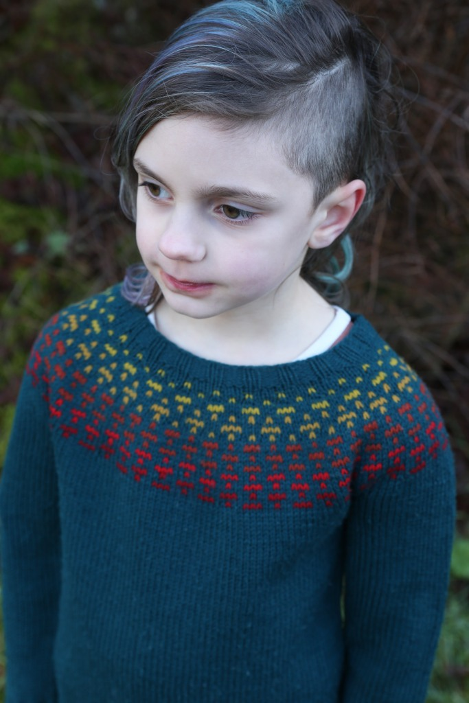 A child in a teal sweater with a warm ombre of colourwork at the yoke.