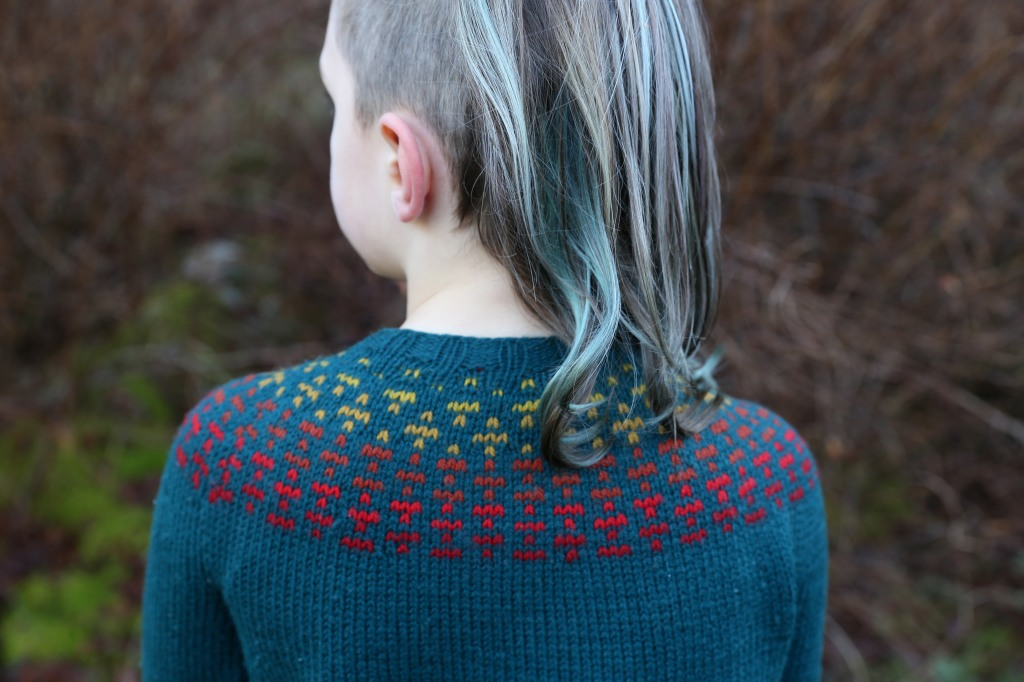 A child facing away from the camera in a teal sweater with a warm ombre of colourwork.