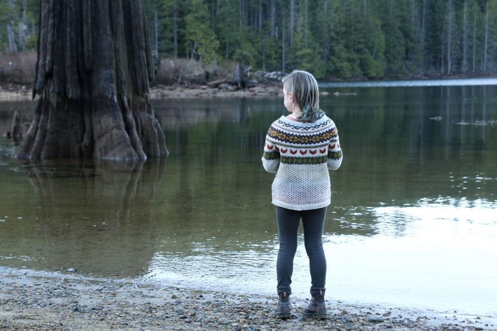 A child by a lake in a colourwork sweater