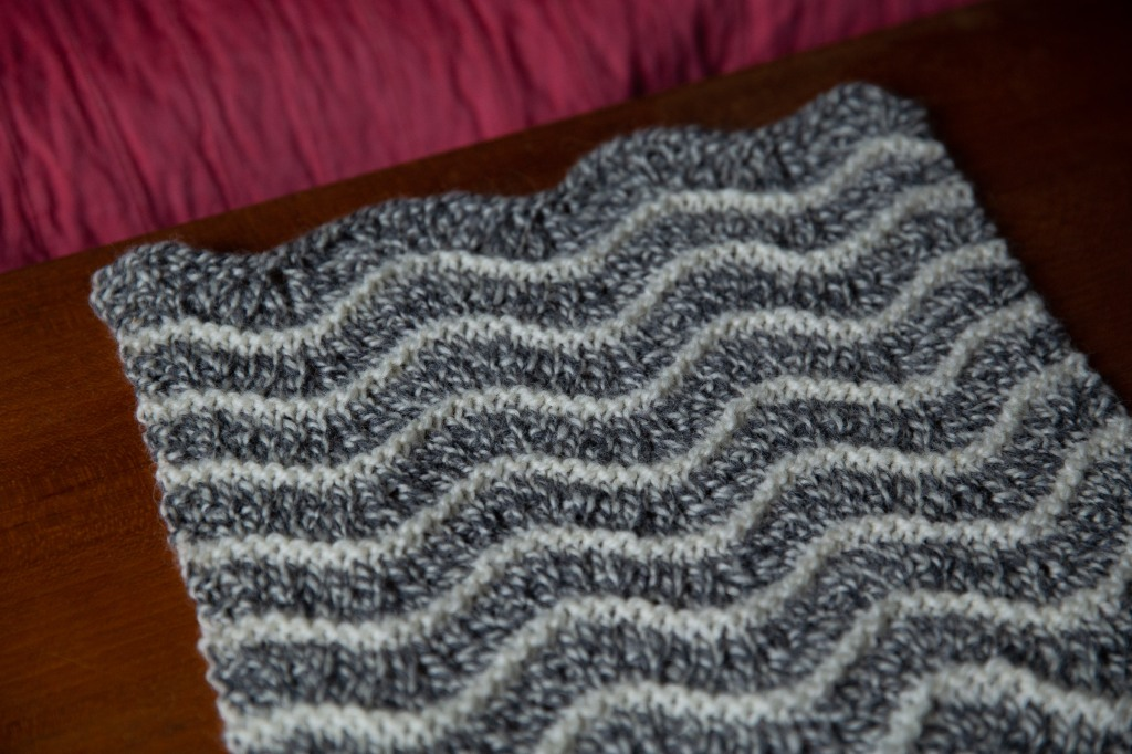 Wavy striped swatch in black and white marled yarn with white garter stitch lines between.