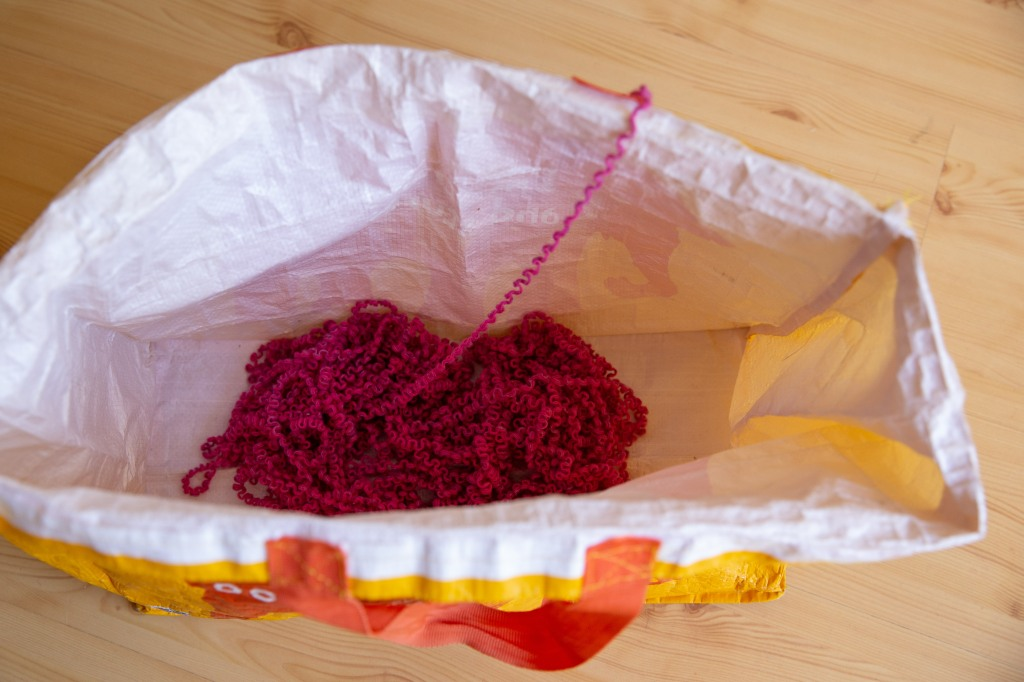 a shopping bag with yarn spaghetti inside