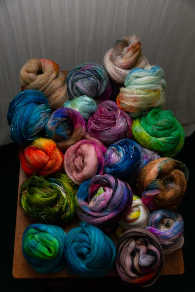 Dozens of small nests of colourful hand-dyed fibre piled on a table in all shades of the rainbow.