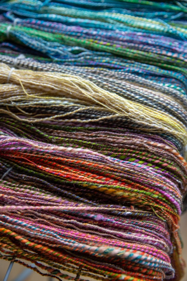 Two-ply handspun in a rainbow of vivid shades piled on a drying rack.